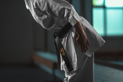 Close Up Karate girl with black belt displaying respect - on belt Kaishin wich means