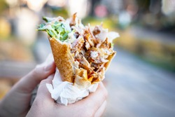Close up kebab holding with human hands. Eating fast food on the city street. Outdoors, copy space.