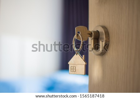 close up key on the door with morning light, personal loan concept. subject is blurry.