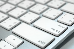 Close up keyboard of a computer on focus at enter button (English - Thai language)