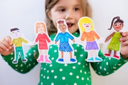 Close-up kid girl holding paper homemade garland with painted children of different races. Happy  international  children s day