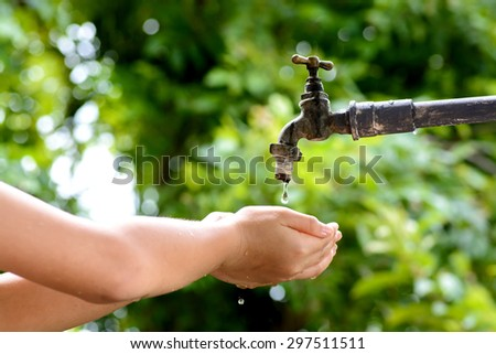 Close up kid hand wait for water drop from old grunge brass faucet on green bokeh from tree background. Water shortage and earth day concept.