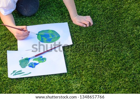 Close up kids hand drawing a picture of earth globe.Child painting with brush and watercolor paints a picture of earth.Earth day, plastic free and zero waste concept.