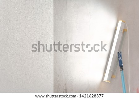 Close-up lamp for detection of irregularities. Worker glueing wallpapers on concrete wall. Repair the apartment. Home renovation concept. White Wallpaper for paint
