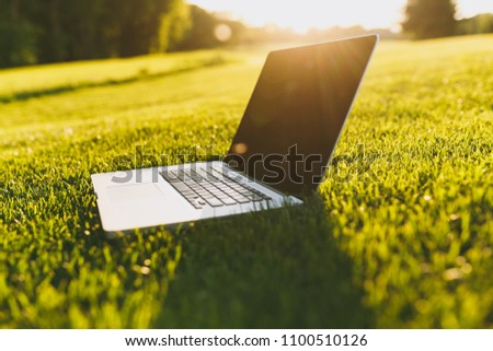 Close up laptop pc computer with blank black empty screen to copy space in park on vibrant spring green fresh grass, sunshine lawn meadow outdoors on nature. Mobile Office. Freelance business concept #1100510126