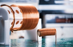 Close-up large and small coils with copper wire stand on a green microcircuit at a factory of classified military equipment. Super secret high-frequency components and equipment concept