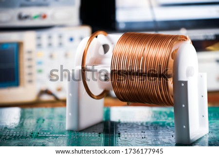 Close-up large and small coils with copper wire stand on a green microcircuit at a factory of classified military equipment. Super secret high-frequency components and equipment concept ストックフォト ©