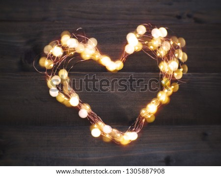 Close up LED lighting and wire frame heart shape on brown wood with copy space. Love concept. Valentines day and wedding background. #1305887908