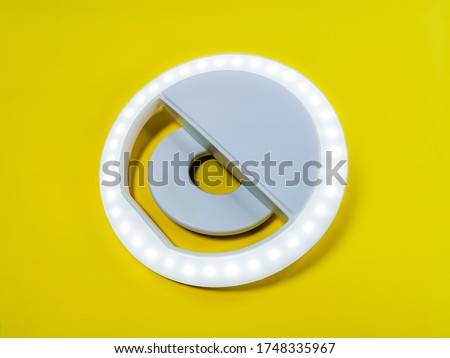 Close-up LED selfie circular ring light lamp on a yellow background. Clip-on flash light camera phone for taking selfie photos and videos. Compact and lightweight device for bloggers and vloggers.