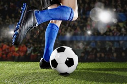 close up legs and feet of football player in action wearing blue socks and black shoes running and dribbling with the ball playing match on green grass pitch at  soccer stadium with flashes and flares