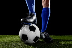 close up legs and feet of football player in blue socks and black shoes posing with the ball playing on green grass pitch isolated on black background