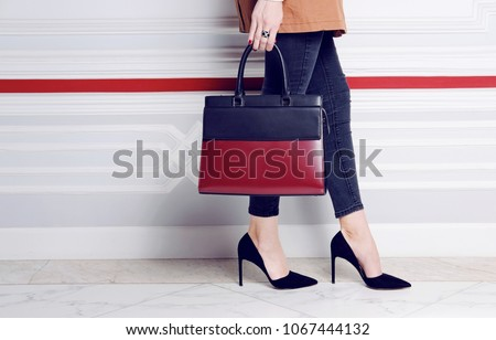 Close up legs fashion woman in heel shoes with big handbag in hand. Autumn trench coat outfit