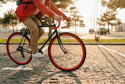 close up legs in sneakers and hands on steering wheel of hipster style bearded man in red hoodie and beige trousers riding alone with backpack on bicycle healthy active lifestyle traveler backpacker