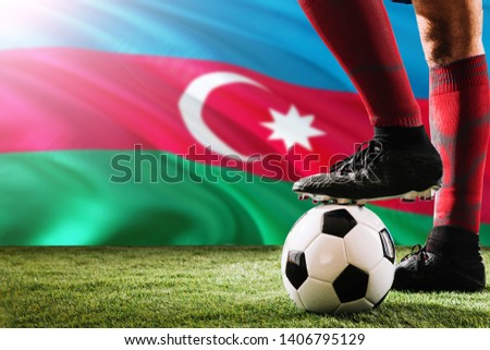 Close up legs of Azerbaijan football team player in red socks, shoes on soccer ball at the free kick or penalty spot playing on grass. #1406795129