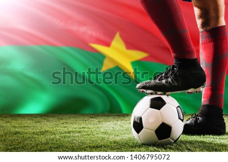 Close up legs of Burkina Faso football team player in red socks, shoes on soccer ball at the free kick or penalty spot playing on grass. #1406795072