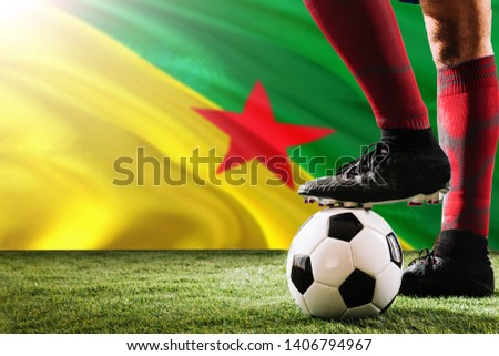 Close up legs of French Guiana football team player in red socks, shoes on soccer ball at the free kick or penalty spot playing on grass. #1406794967