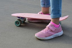 Close-up legs of  girl skateboarder in blue jeans and pink sneakers, riding  pink penny skate longboard. International Skateboarding Day. Selective focus