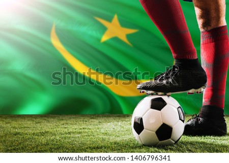 Close up legs of Mauritania football team player in red socks, shoes on soccer ball at the free kick or penalty spot playing on grass. #1406796341