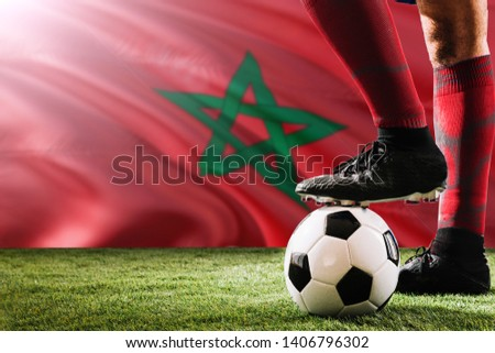 Close up legs of Morocco football team player in red socks, shoes on soccer ball at the free kick or penalty spot playing on grass. #1406796302