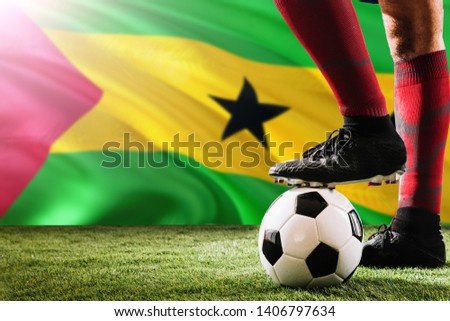 Close up legs of Sao Tome And Principe football team player in red socks, shoes on soccer ball at the free kick or penalty spot playing on grass. #1406797634