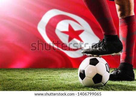 Close up legs of Tunisia football team player in red socks, shoes on soccer ball at the free kick or penalty spot playing on grass. #1406799065