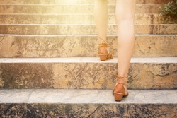 Close up legs of young woman walking stepping up stair in attractions. Feet and leg of young woman wearing brown high going up the stairs outdoors. Alone travel concept