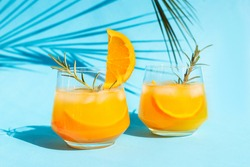Close-up lemonade, orange cocktail, refreshing summer drink with ice in a glass with a sprig of rosemary on a blue background under a palm leaf on a bright sunny day.