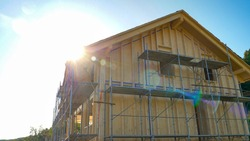 CLOSE UP, LENS FLARE: Bright spring sunbeams shine on a large wooden house being built in countryside. Scenic view of an unfinished cross-laminated timber house being built in rural area on sunny day.