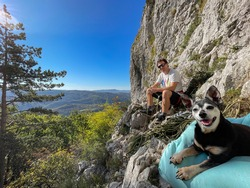 CLOSE UP, LENS FLARE, COPY SPACE: Adorable shot of a climber and his miniature pinscher resting during their fun climbing trip. Cheerful man and his senior dog rest while rock climbing in Crni Kal.