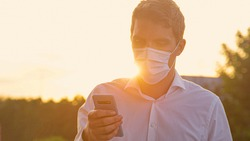 CLOSE UP, LENS FLARE, DOF: Millennial wearing a protective surgical mask checks his smartphone at golden sunset. Young Caucasian man wearing a medical facemask texts on a sunny summer evening.