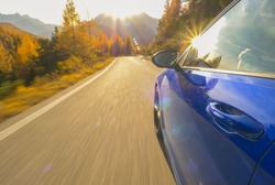 CLOSE UP, LENS FLARE: Idyllic view of sunlit Dolomites as blue sportscar drives down scenic road. Cinematic shot of golden sunbeams reflecting in the shiny door of a car cruising down mountain road.