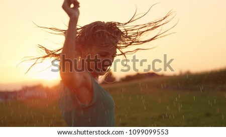 CLOSE UP, LENS FLARE: Joyful blonde girl enjoys her evening in the countryside by dancing in the rain. Stunning golden sun rays shine on playful young woman spinning and enjoying a spring shower.