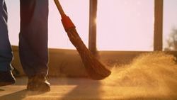 CLOSE UP, LENS FLARE, LOW ANGLE: Contractor is sweeping the dirty floor with a retro straw broom at scenic golden sunset. Worker sweeps the dusty floor after a long day at a busy construction site.