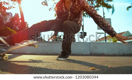 CLOSE UP, LENS FLARE: Unrecognizable young man fails to land a tough trick with his skateboard. Cool skater dude slams to the concrete pavement after failing to do flip trick in the urban skate park.