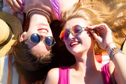 Close up lifestyle fashion portrait of two pretty fresh young brunette and blonde best friends girls,having vacation on the tropical island beach,wearing bikini sunglasses and bright jewelry
