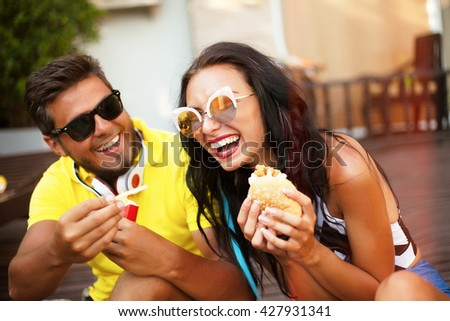 Close up lifestyle funny portrait of couple laughing and having fun together,funny date with burgers and french fry,funny mood and crazy emotions,man joke of her girlfriend,feed her and shows tongue