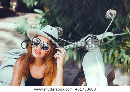 Close up lifestyle image of young fashionable woman in casual outfit sitting on scooter on the street. Wearing blue shirt, white pants, trendy sunglasses. Tourist woman enjoying holidays #481750603