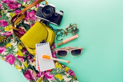 Close up lifestyle photo of hipster student accessories . Still life of random objects of modern girl / woman. Leather bag, camera, Sunglasses, paper notepad, Aerial view. Sunny summer colors.