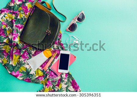 Close up lifestyle photo of hipster student accessories . Still life of random objects of modern girl / woman. Leather bag, camera, Sunglasses,t, Aerial view. Sunny summer colors.  Tropical print.