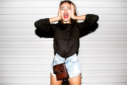 Close up lifestyle portrait of bad girl hipster girl making funny face and showing her tongue.Laughing portrait,crazy mood,covers ears and shouts,beats,beat box,music speakers,loud music,deep house