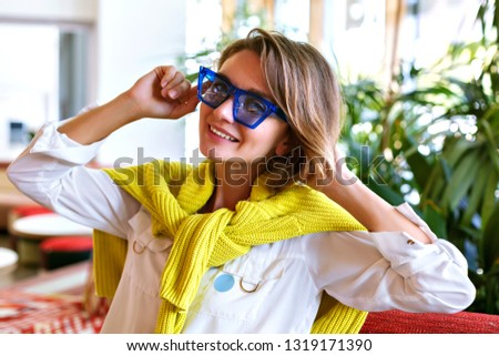 Close up lifestyle portrait of pretty woman with pretty face, wearing trendy blue cat eye sunglasses, white shirt and yellow sweater, interior with palm trees.