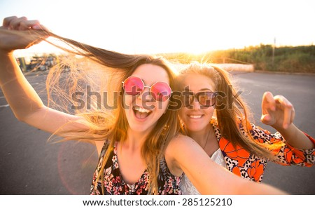 close-up lifestyle portrait of young best friends girls having fun at cool sunset.Travel concept,happy girls make picture together and having fun,laughing and make funny faces on camera,sunshine girls