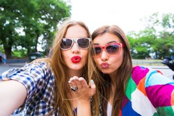 Close up lifestyle selfie portrait of pretty fresh young brunette and blonde best friends girls making selfie,having fun,sending kisses,wearing sunglasses. Fresh make-up,teenage outfit,summer vacation