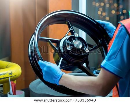 Close up light alloy car wheel in process QC worker checking dish rim. Stock fotó ©