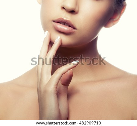 Close-up lips and shoulders of young caucasian girl with natural make-up, perfect skin and green eyes touch her skin isolated on white background. Studio portrait. Toned #482909710