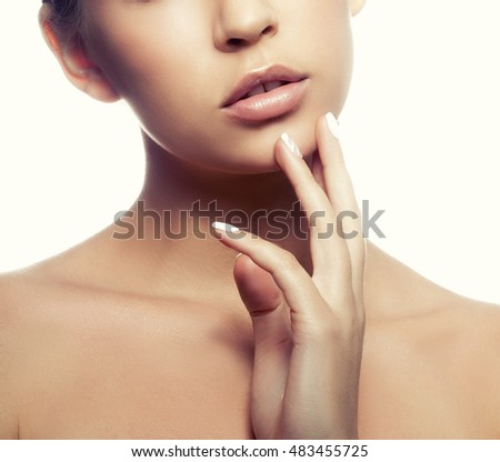Close-up lips and shoulders of young caucasian girl with natural make-up, perfect skin and green eyes touch her skin isolated on white background. Studio portrait. Toned #483455725