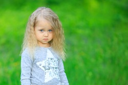 Close up little blonde girl of four 4 years old sulking outdoors in summer. Sad cute vulnerable offended kid with big blue eyes on blurred green background. Children Protection Day. Hopeful concept