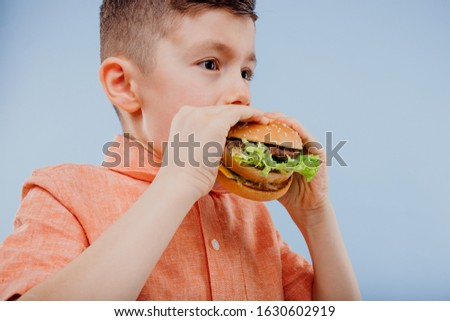 close up little boy eats a burger. fast food and junk food. look with taste. kids love burgers. isolated on blue background. studio. look at the camera Imagine de stoc ©