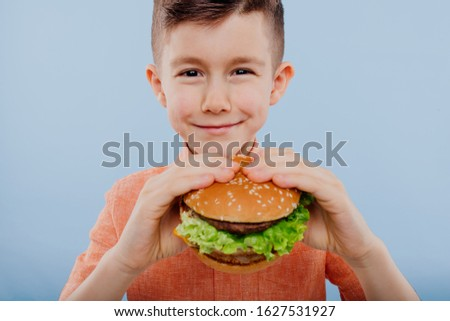 close up little boy with burger in hand. fast food and junk food. look with taste. kids love burgers. isolated on blue background. studio. look at the camera, cropped Imagine de stoc ©