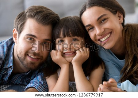 Close up little cute daughter holding hands on chin lying on warm floor with young parents in living room at home married couple sweet child smiling and looking at camera. Happy diverse family concept